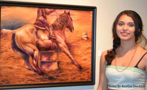 "Work of art: Twenty-one year old Cameron student Karyn Ortega proudly poses in front of her painting ""Barrel Race"" during the show on Nov. 9."
