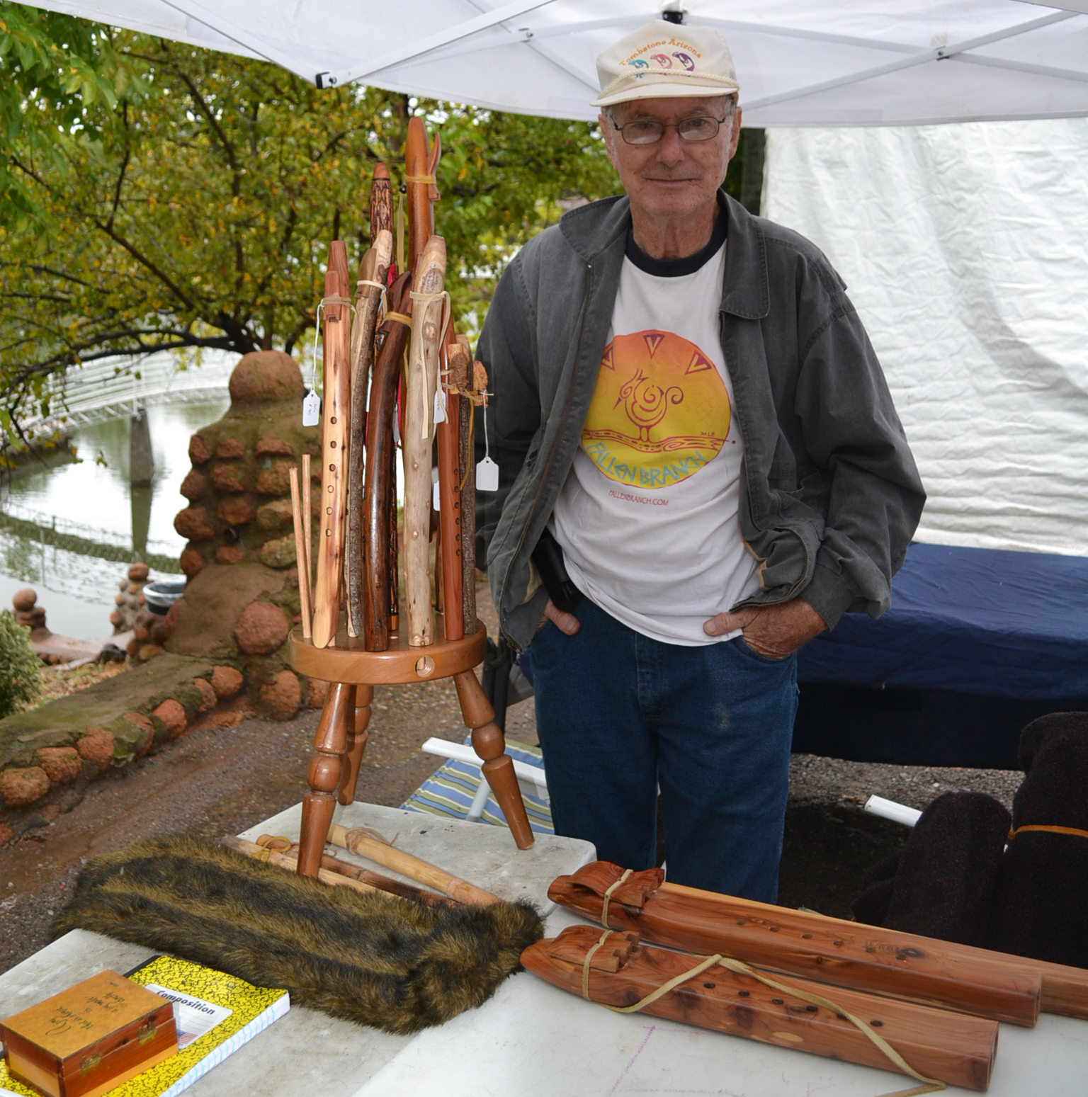 John Suttles showcases a variety of flutes, some of which he made, with Medicine Creek as a backdrop. Creeping Bear and Suttles were two of the many artists on display during the sixth annual Medicine Park Art Walk and Flute Festival on Sept. 19 and 20 in Medicine Park.