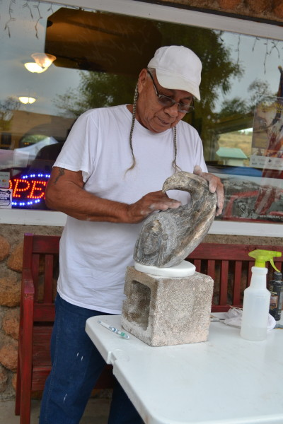 Bobby Creeping Bear demonstrates his carving techniques with an alabaster sculpture in front of one of Medicine Park's creekside shops.
